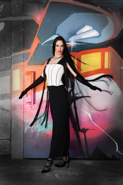 Model mit langem, dunklen Haar vor einer Graffitiwand, sie trägt ein außergewöhnliches und schönes Kleid