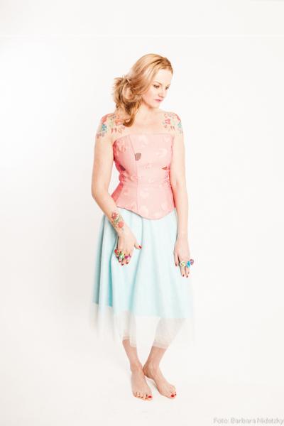 blondrotes Model trägt pastellfarbene, zarte Kleider von Aniko Smart Couture, Studiofoto