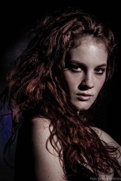 dunkles eher mystisches Modefoto, rothaariges lockiges Model, in dunkler Wäsche