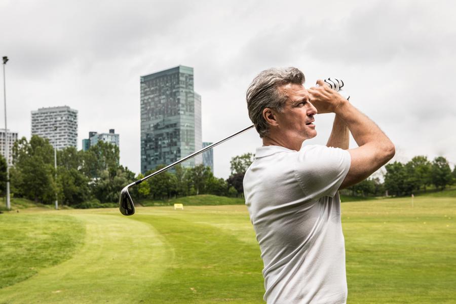 Modefoto eines Golfers am Green im Hintergrund stehen Hochhäuser
