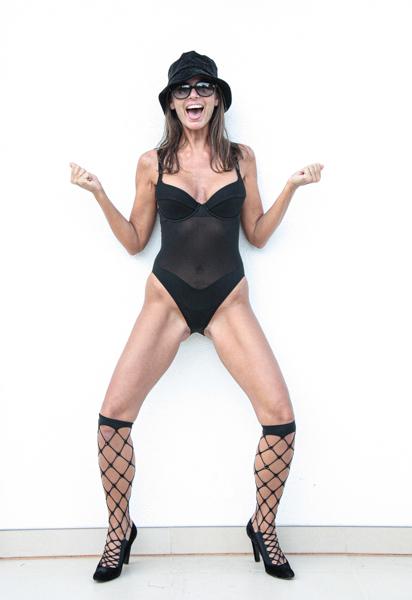 brünettes Model lacht frech und tanzt, trägt Sonnenbrillen, schwarzen Hut, und einen sexy schwarzen Wolfordbadeanzug