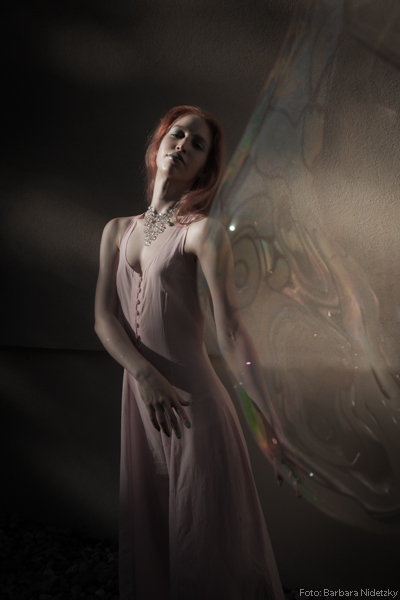 junge, rothaarige Frau wird etwas mystisch und entrückt dargestellt, Modefoto, Kunstfoto, mit Riesenseifenblasen