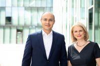 2 Rechtsanwälte, Frau und Mann stehen vor einer modernen Glasfassade
