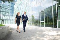 2 Rechtsanwälte, Frau und Mann gehen vor einer modernen Glasfassade