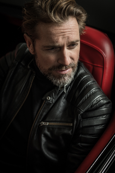 Model Michael Urban in einer Corvette, cool,lässig in schwarzer Lederjacke