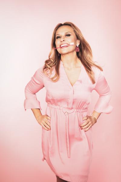 Schöne Zahnärztin im rosa Kleid posiert lustig mit Zahnbürsten