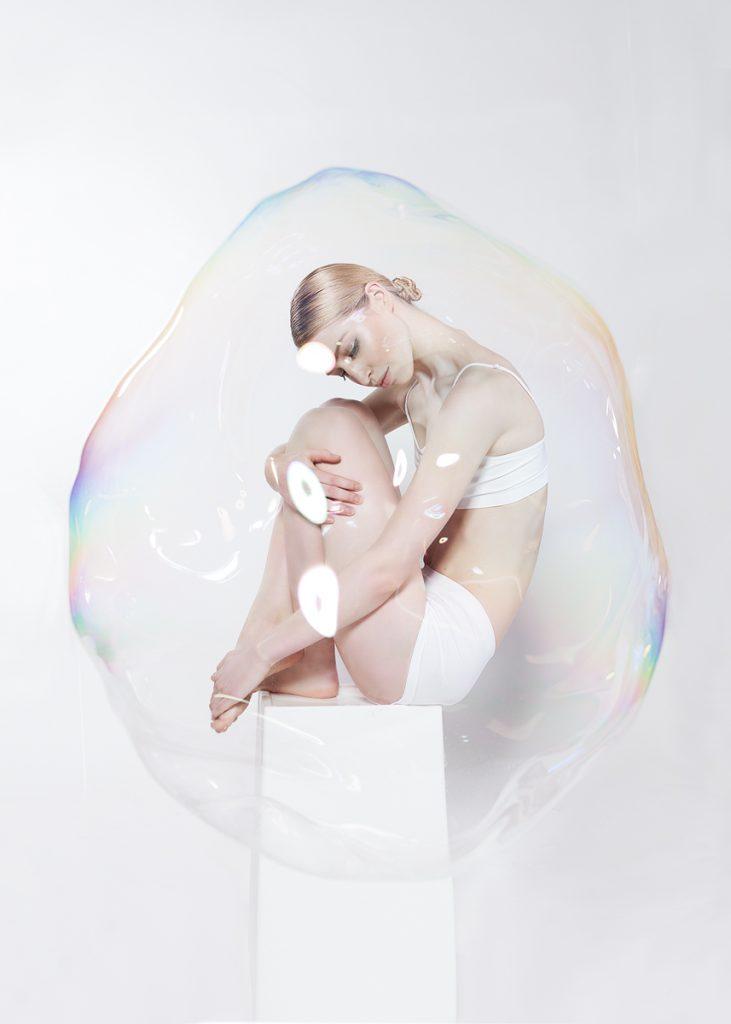 schöne Frau scheint in einer Riesenseifenblase zu sitzen