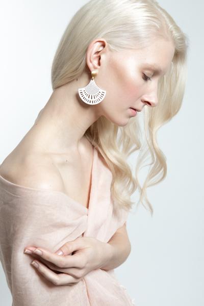 Schönes blondes Model mit Elfenbeinhaut trägt schöne, ornamentale Ohrringe in bunten Farben