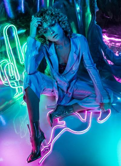 High Fashion Photo, schönes blondes Model im stylischen Hosenanzug, buntes Licht, Hologramm-Hintergrund, leuchtende Neonröhren