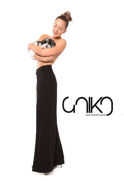 Modefoto für Aniko Smart Couture, Model trägt schöne schwarze Hose ohne Oberteil und hält einen kleinen Hund vor ihrer Brust