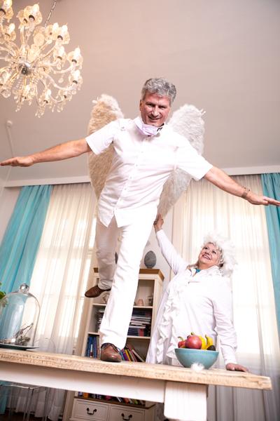 Zahnarzt Dr. Georg Piehslinger steht als Engel verkleidet , auf einem Fuß am Tisch im Warteraum